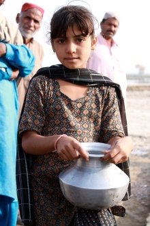 A young girl in Pakistan's Sindh province lines up for clean drinking water provided by UKaid. Image via Department for International Development.