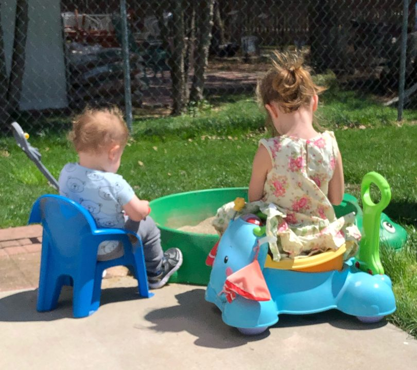 two children sitting side by side next to a sandbox, backs to the camera