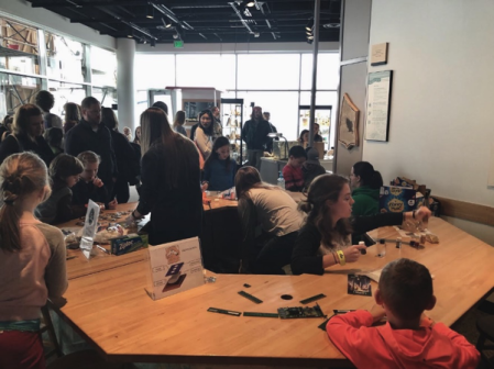 crowds of kids and adults looking at different areas of the s'mores demo spread out on large tables