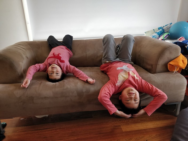 Pictured are two children laying upside down on the back of a couch