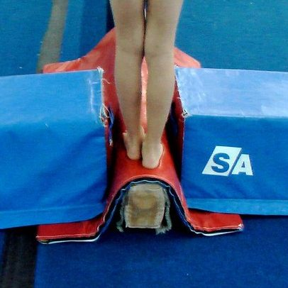 Feet on a balance beam, which is on the floor.