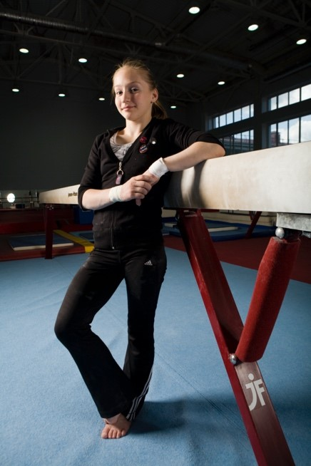 Pictured is gymnast Semenova Ksenia leaning against a tall balance beam lifted off the ground.