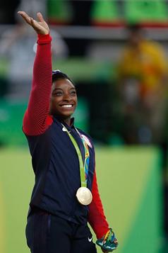 Simone Biles waving wearing a gold medal.