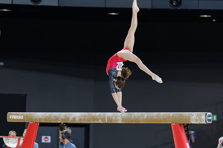 Gymnast Andreea Munteanu on the balance beam. Hands are touching the beam as legs are split in the air.