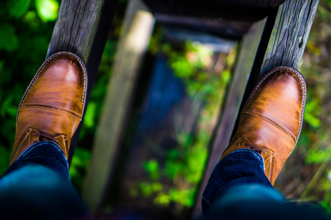 Feet on two planks of wood with a large gap in-between. The gap is a long way down to the forest below.