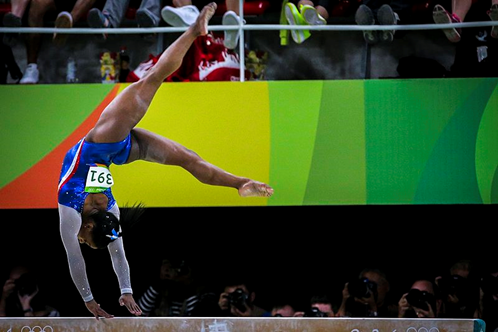 Pictured is simone biles on the balance beam with hand on the beam, and legs spread apart in the air. .