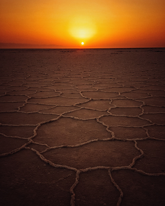 Picture of an orange and yellow sunset over cracked ground similar to that of a dried up river.